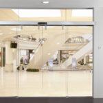 Скляна автоматична розсувна система дверей у виконанні німецької фурнітури Dorma на скляній перегородці. Можлива реалізація системи безпосередньо на проєм